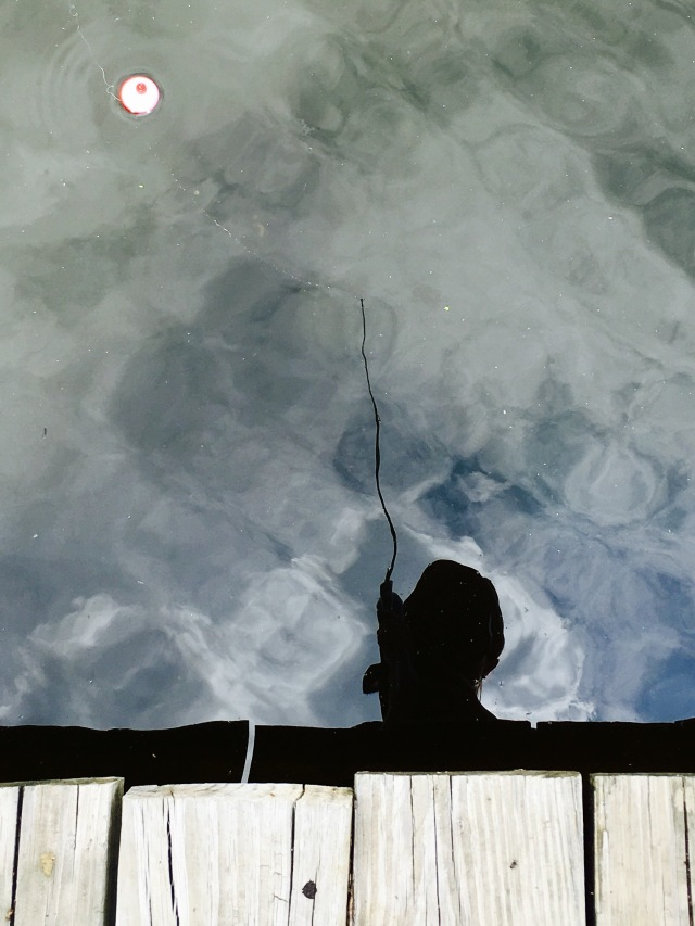 shadow of fisherman in the water with float visible on the water surface